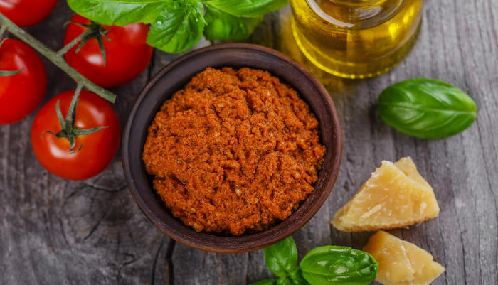 Rød pesto med diverse ingredienser rundt
